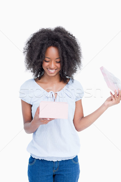 Smiling young woman looking at her birthday present against a white background Stock photo © wavebreak_media