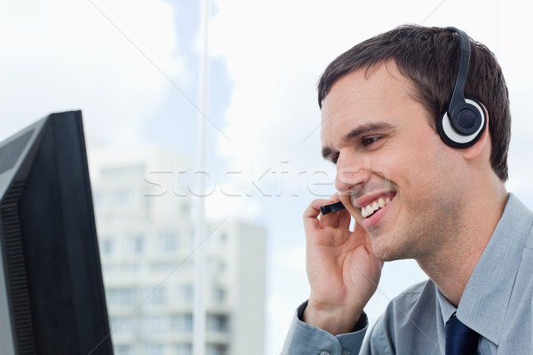 Smiling office worker using a headset in his office Stock photo © wavebreak_media