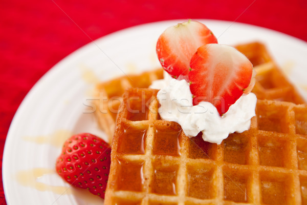 Half cut strawberry and whipped cream on a white plate on a red napkin Stock photo © wavebreak_media