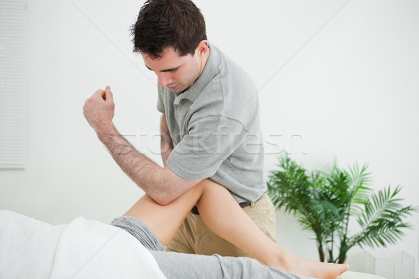 Brown-haired physiotherapist massaging the leg of a woman in a room Stock photo © wavebreak_media