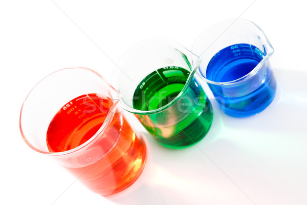 Three beakers of different colour and size against a white background Stock photo © wavebreak_media