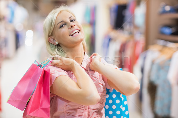 Woman holding bags in her hands smiling in a shop Stock photo © wavebreak_media