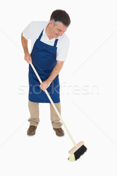 Sweeping man in blue apron Stock photo © wavebreak_media
