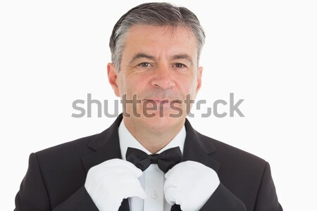 Smiling waiter adjusting his bow tie in front of camera Stock photo © wavebreak_media