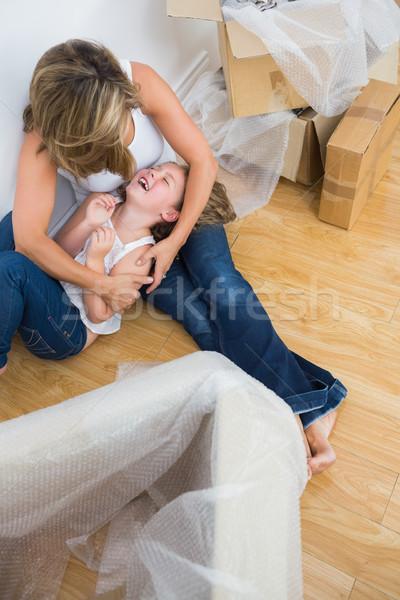 Mother tickling her daughter on the floor Stock photo © wavebreak_media