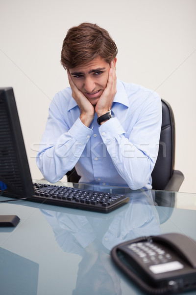Young worried business man sitting at office desk Stock photo © wavebreak_media