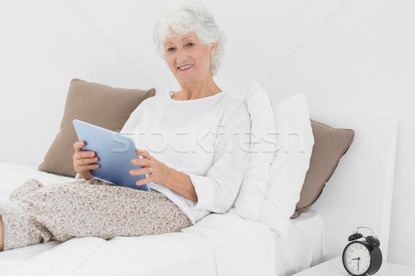 улыбаясь цифровой таблетка кровать домой Сток-фото © wavebreak_media