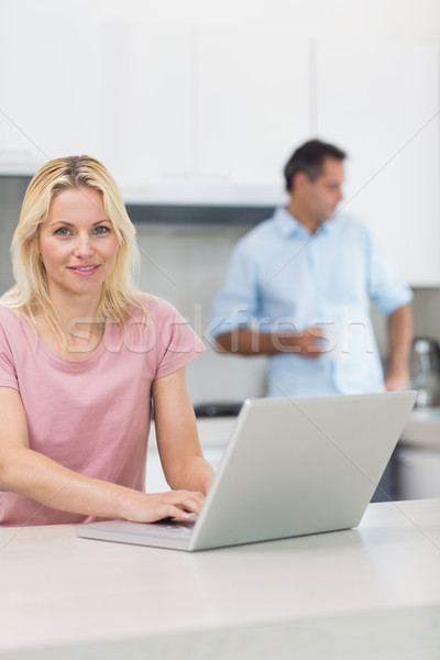 Stock photo: Woman using laptop with man drinking coffee in kitchen