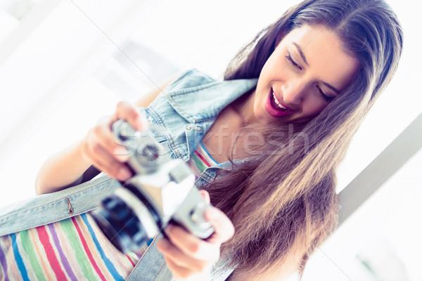Cheerful brunette looking at her camera Stock photo © wavebreak_media
