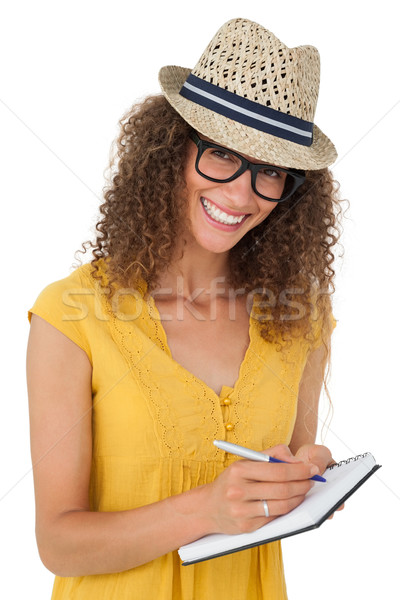 Cheerful young woman writing in notepad Stock photo © wavebreak_media
