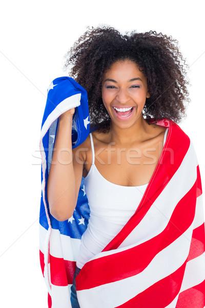 Pretty girl wrapped in american flag smiling at camera Stock photo © wavebreak_media