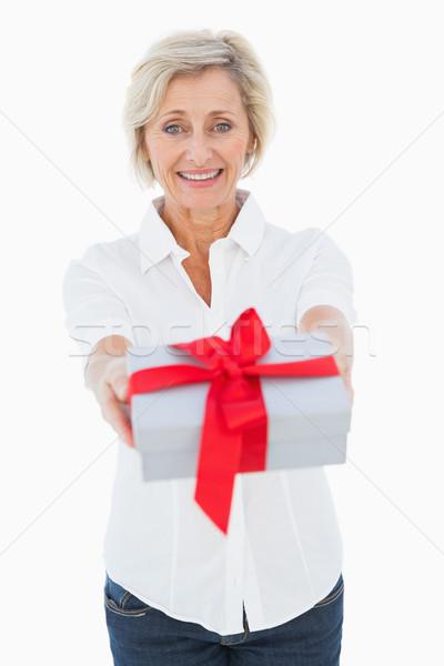 Mature blonde smiling at camera holding gift Stock photo © wavebreak_media
