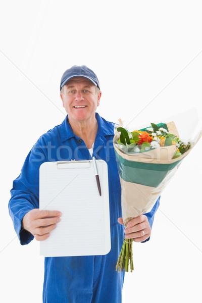Happy flower delivery man showing clipboard Stock photo © wavebreak_media