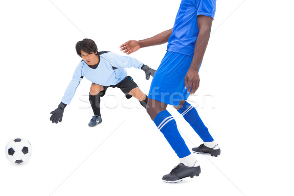 Football player in blue striking at keeper Stock photo © wavebreak_media