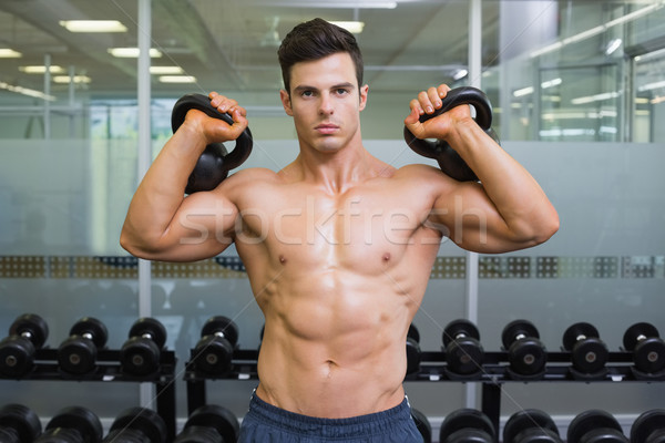 Muscular man lifting kettle bells in gym Stock photo © wavebreak_media