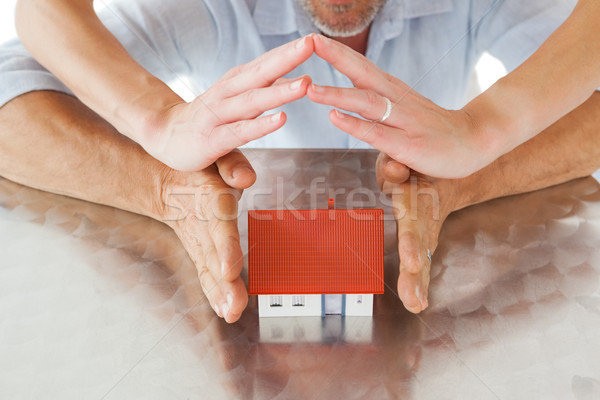 Couple sheltering miniature house with hands Stock photo © wavebreak_media