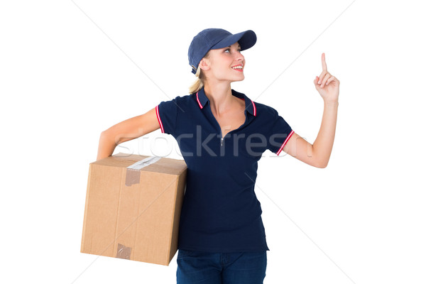 Happy delivery woman holding cardboard box and pointing up Stock photo © wavebreak_media