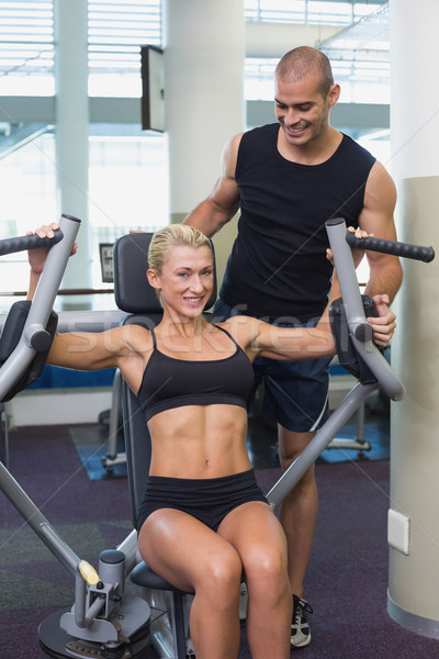 Trainer assisting woman on fitness machine at gym Stock photo © wavebreak_media