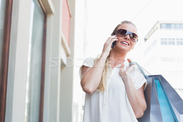 Csinos szőke nő készít hívás tart bevásárlótáskák Stock fotó © wavebreak_media