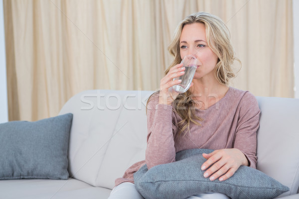 Pretty blonde sitting on couch drinking water Stock photo © wavebreak_media