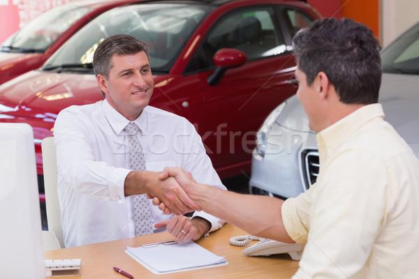 Smiling salesman shaking a customer hand Stock photo © wavebreak_media
