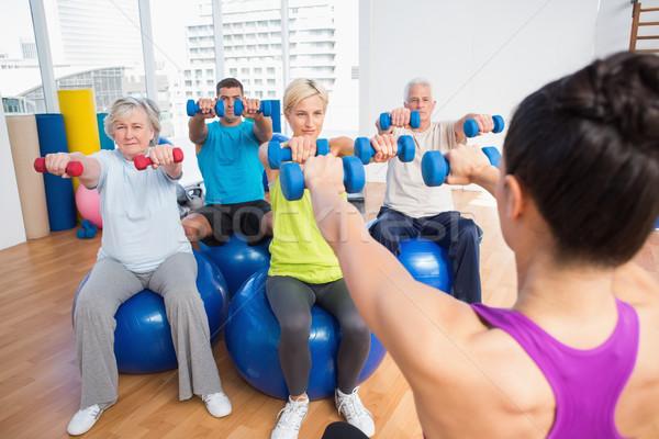 Instructor with class lifting dumbbells Stock photo © wavebreak_media