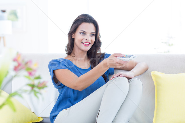Smiling beautiful brunette relaxing on the couch and changing tv Stock photo © wavebreak_media
