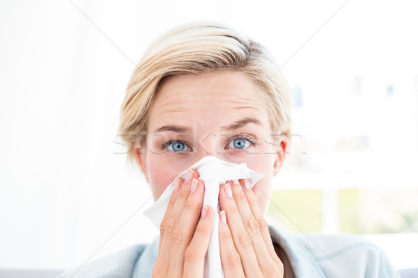 Sick blonde woman blowing her nose Stock photo © wavebreak_media