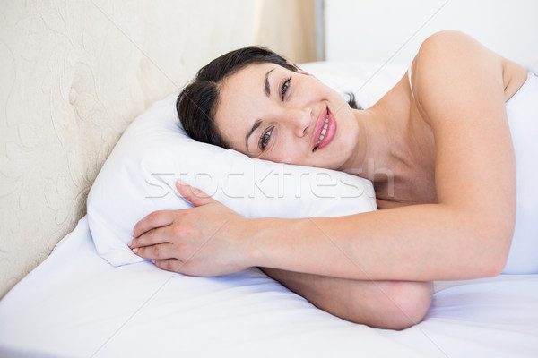 Pretty brunette smiling on bed Stock photo © wavebreak_media