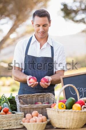 Smiling farmer holding two red apples Stock photo © wavebreak_media