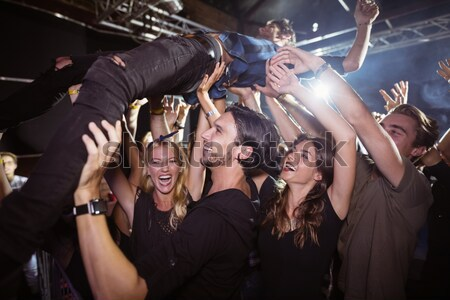Young woman with arms raised enjoying at nightclub Stock photo © wavebreak_media