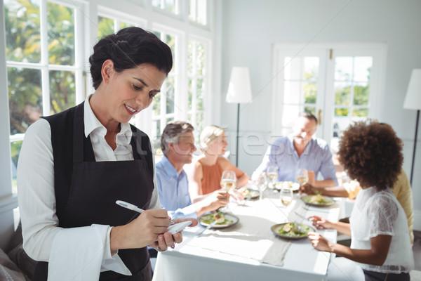 Uśmiechnięty kelnerka piśmie celu notatnika znajomych Zdjęcia stock © wavebreak_media