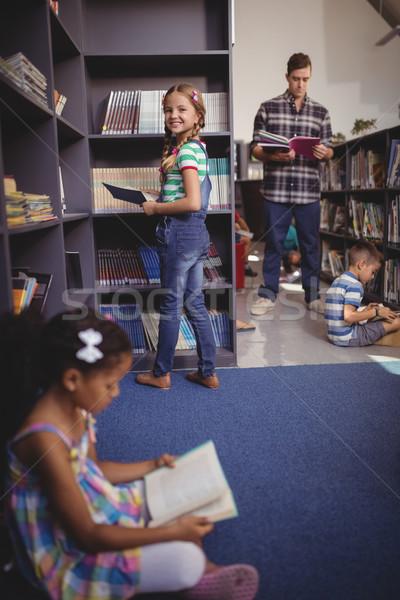Portrait of happy schoolgirl selecting book from bookshelf in library Stock photo © wavebreak_media