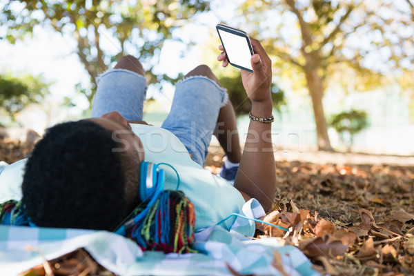 Young man using mobile phone while lying on a picnic blanket Stock photo © wavebreak_media