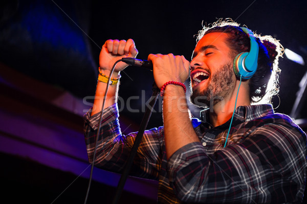 Man listening to headphones while singing on microphone Stock photo © wavebreak_media