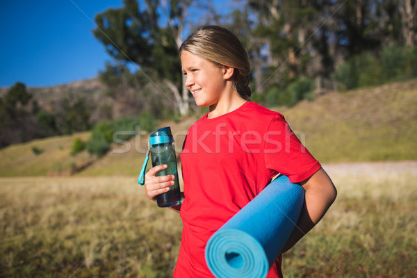 Girl holding a water bottle and exercise mat in the boot camp Stock photo © wavebreak_media