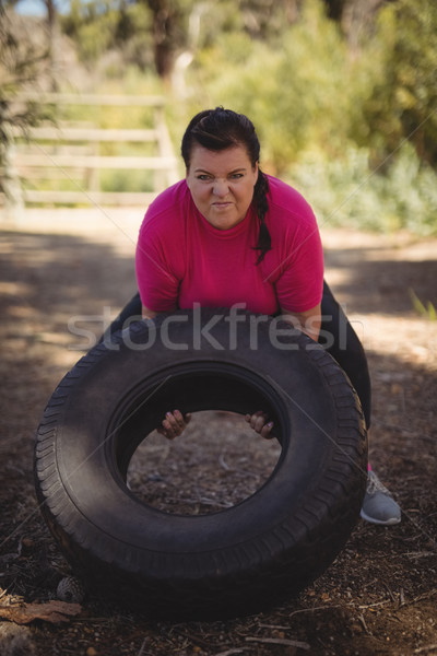 Determined woman exercising with huge tyre during obstacle course Stock photo © wavebreak_media
