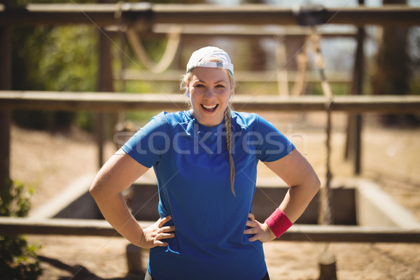 Portrait of happy woman standing with hands on hip during obstacle course Stock photo © wavebreak_media
