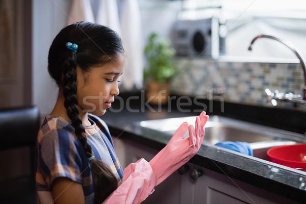 Side view of girl wearing pink rubber gloves in kitchen Stock photo © wavebreak_media