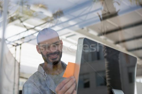 Smiling designer using computer seen through glass Stock photo © wavebreak_media