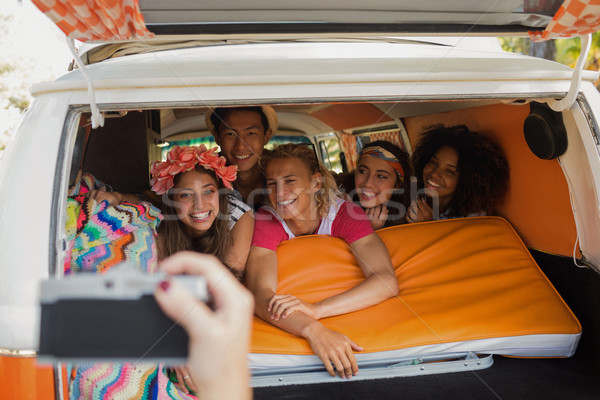 Stock photo: Cropped hand photographing smiling friends in camper van