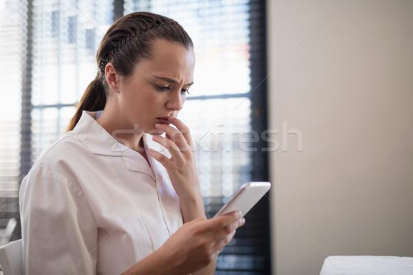 Aggódó fiatal női terapeuta sms üzenetküldés mobiltelefon Stock fotó © wavebreak_media