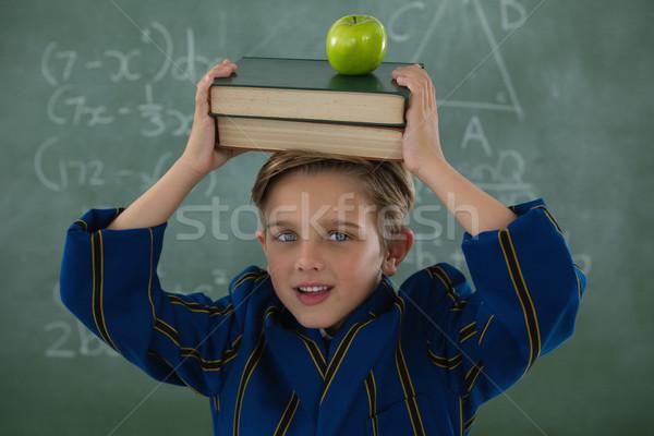 Schoolboy holding books stack with apple against chalkboard Stock photo © wavebreak_media