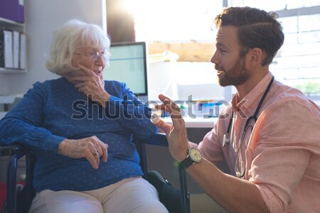 Senior woman blowing candles of cup cake being held by nurse Stock photo © wavebreak_media