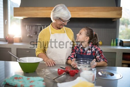 Grandmother and granddaughter adding fresh cut apples to the crust Stock photo © wavebreak_media