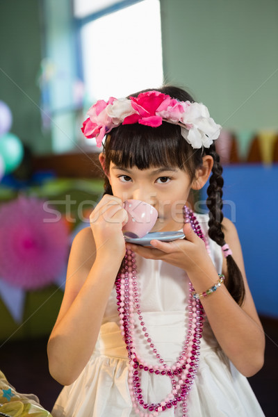 Portrait of cute girl drinking tea during birthday party Stock photo © wavebreak_media