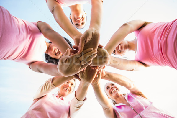 Women wearing pink for breast cancer and putting hands together Stock photo © wavebreak_media