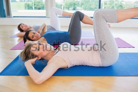 Instructor and student exercising while lying on mat in yoga studio Stock photo © wavebreak_media