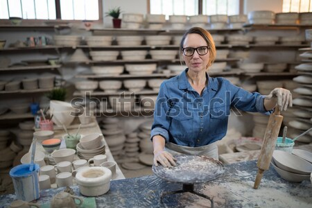 Portrait of female potter standing with mobile phone Stock photo © wavebreak_media