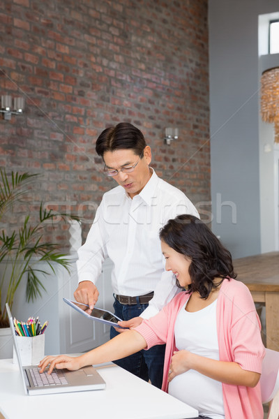Happy man showing tablet to his pregnant wife Stock photo © wavebreak_media